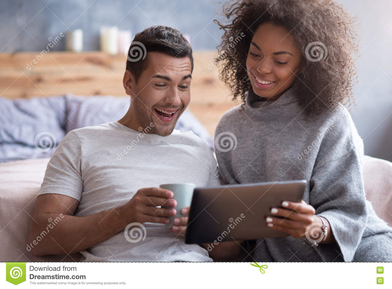 laughing couple watching a film in the bedroom stock photo