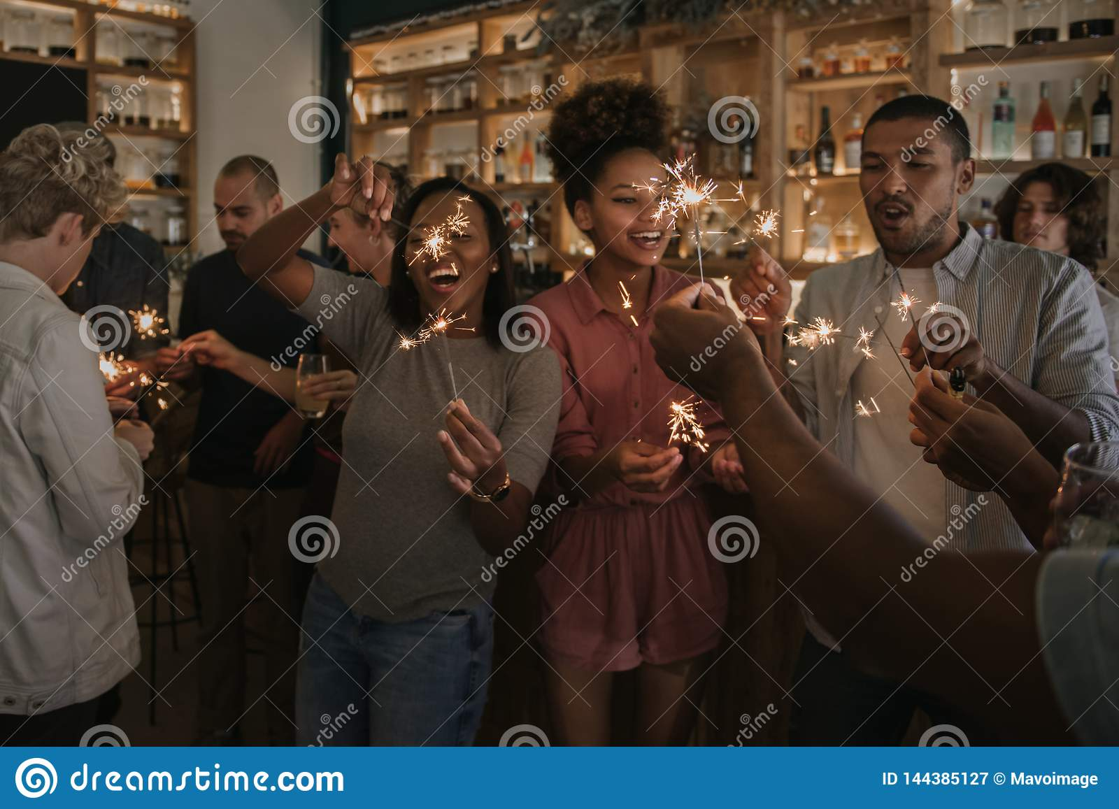 Laughing friends celebrating with sparklers in a bar at night