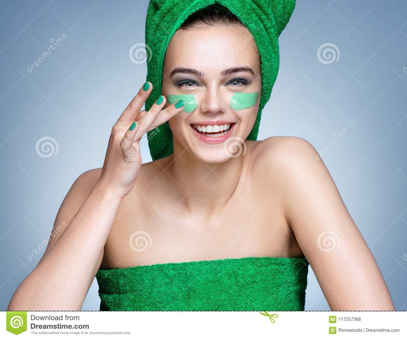 Laughing girl in green towels applying moisturizing cream on her face