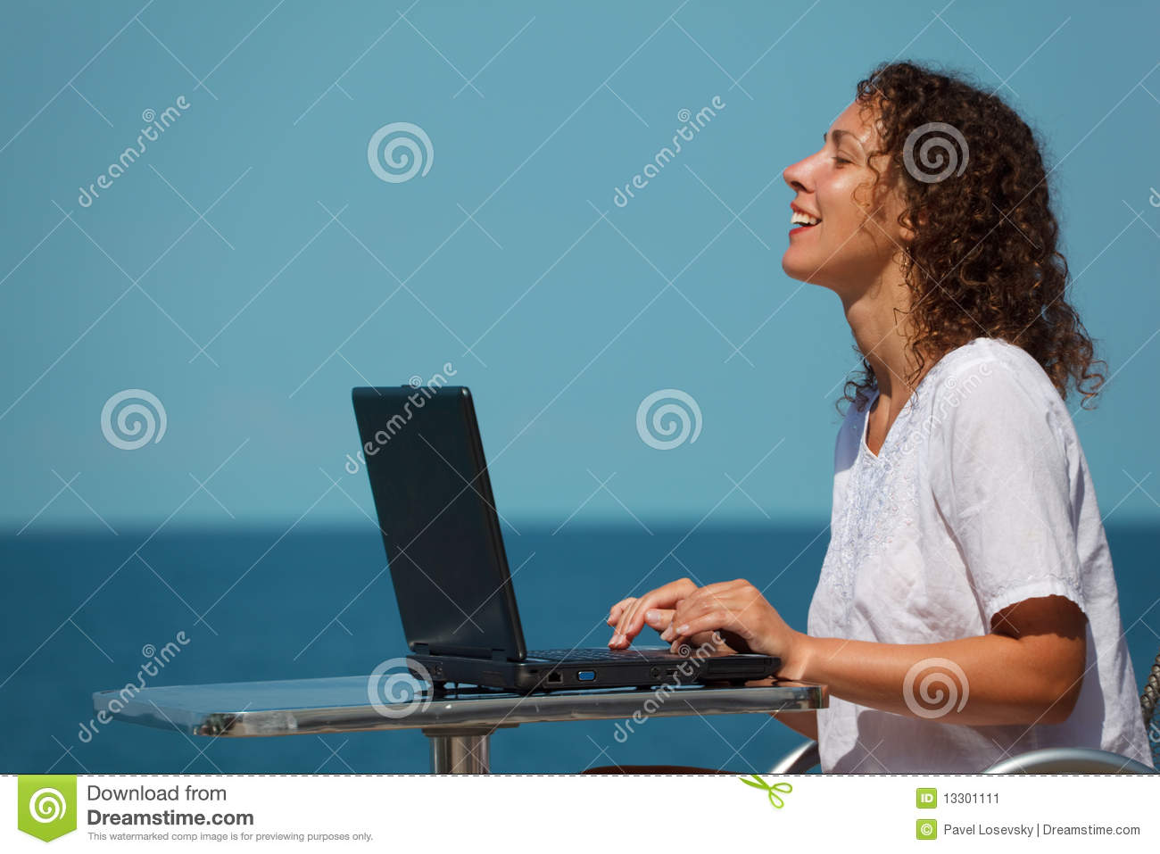 Laughing girl with laptop. Sits at table on beach