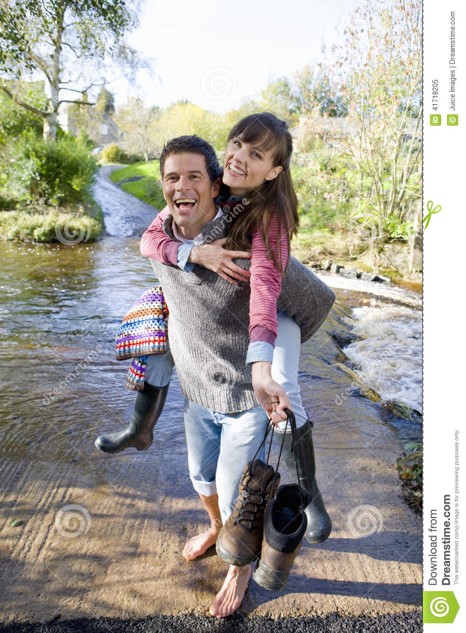 Laughing husband carrying wife through shallow stream