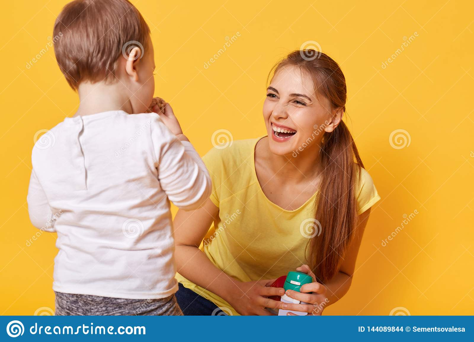 Laughing joyful woman plays with her little cute daughter, spends free time together on the weekends. A young woman is happy to