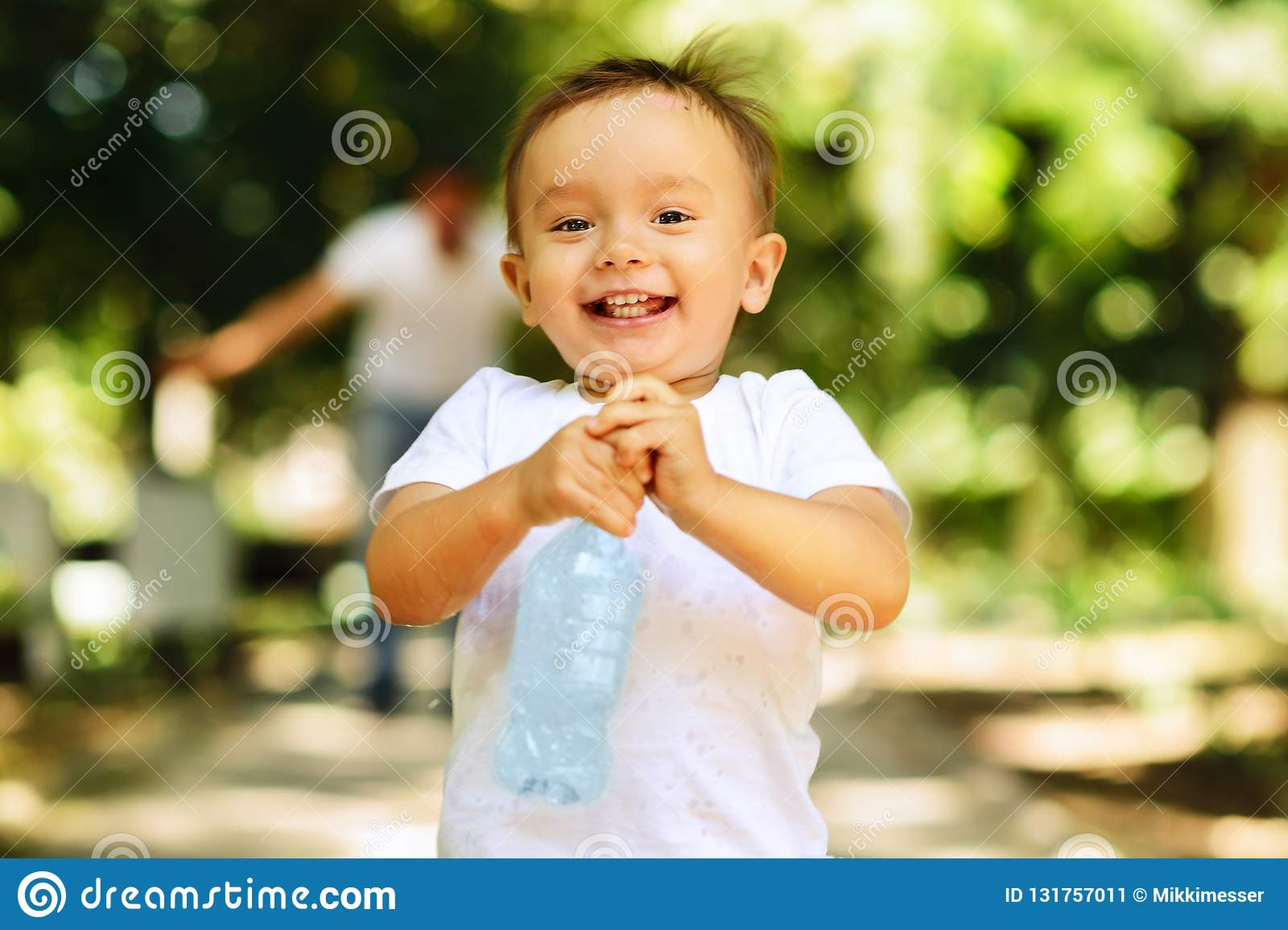 Laughing little boy running outdoor with a bottle of a clear drinking water, his father is blurred in the background. Importance