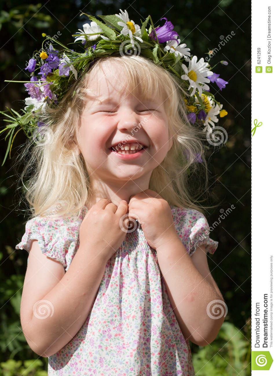 Laughing little girl in flowers wreath