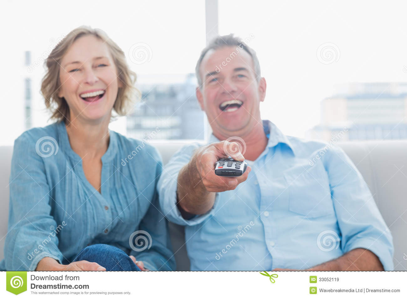 Laughing middle aged couple sitting on the couch watching for Couch 6 personen