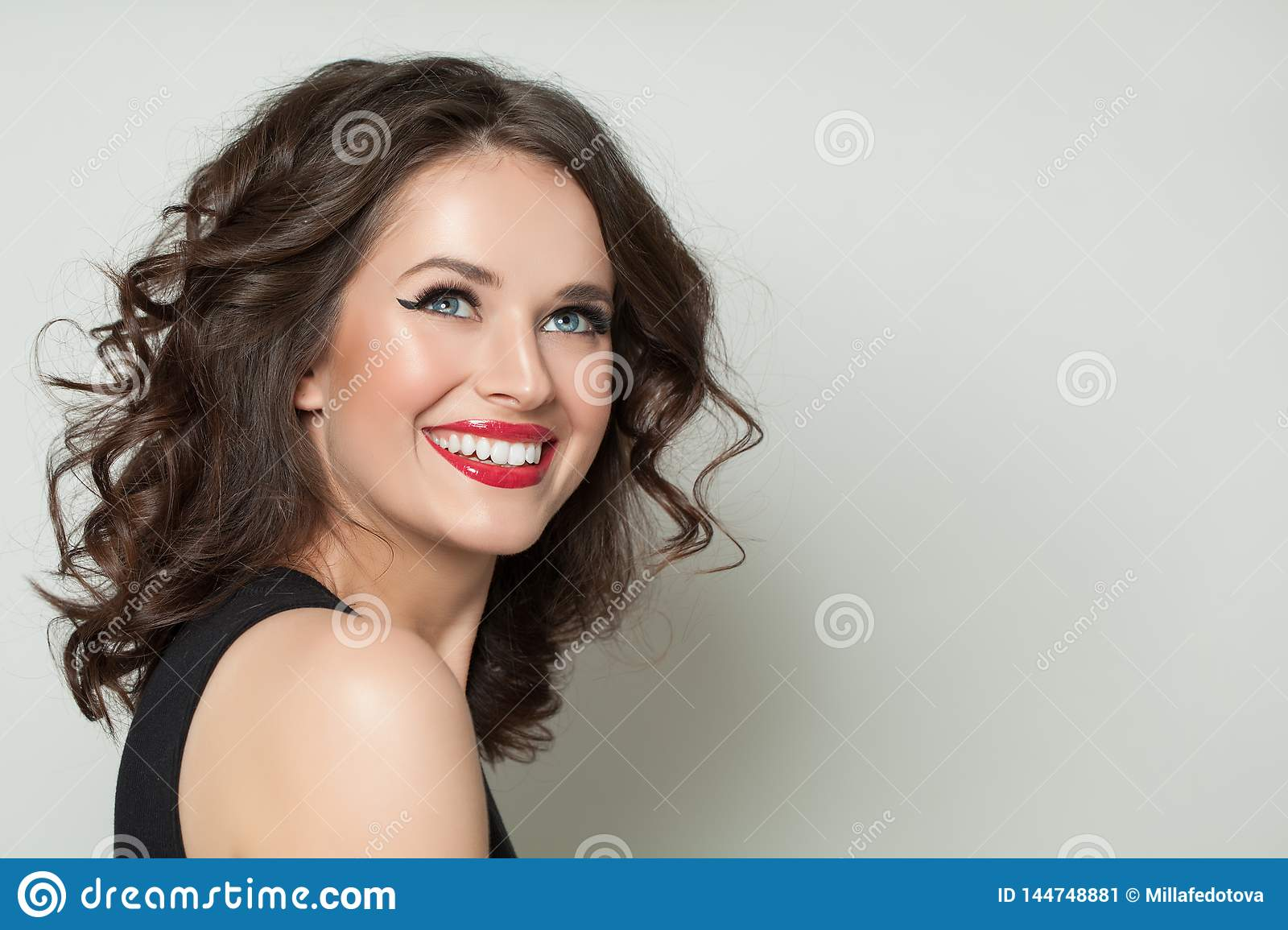 Laughing model woman with makeup and healthy curly hair on white background