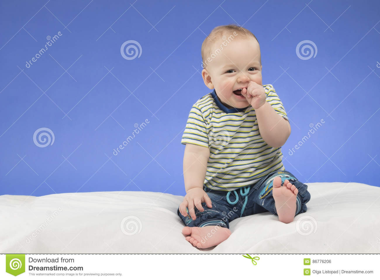 Laughing 8 month old baby boy sitting on the white blanket studio