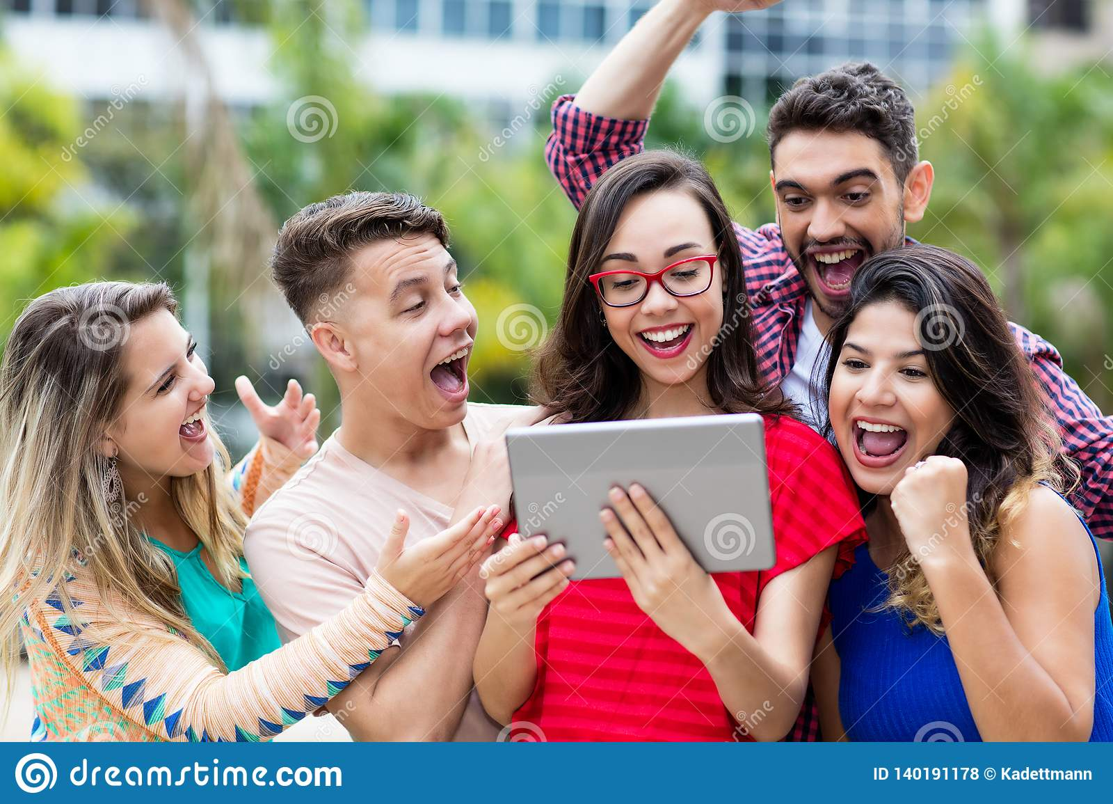 Laughing nerdy french female student with tablet computer and group of cheering international students