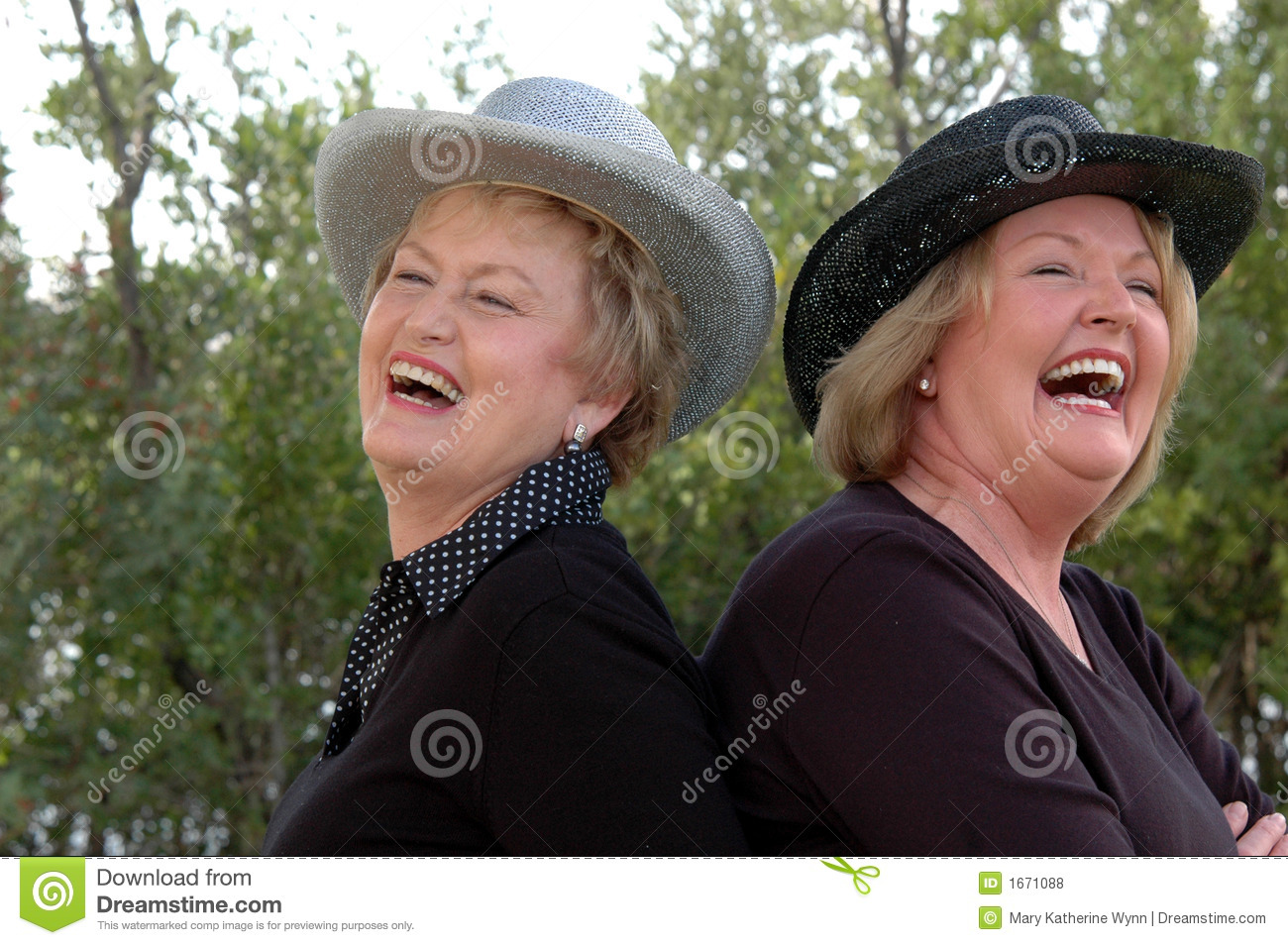 Laughing mature woman wearing cowboy hats, back to back