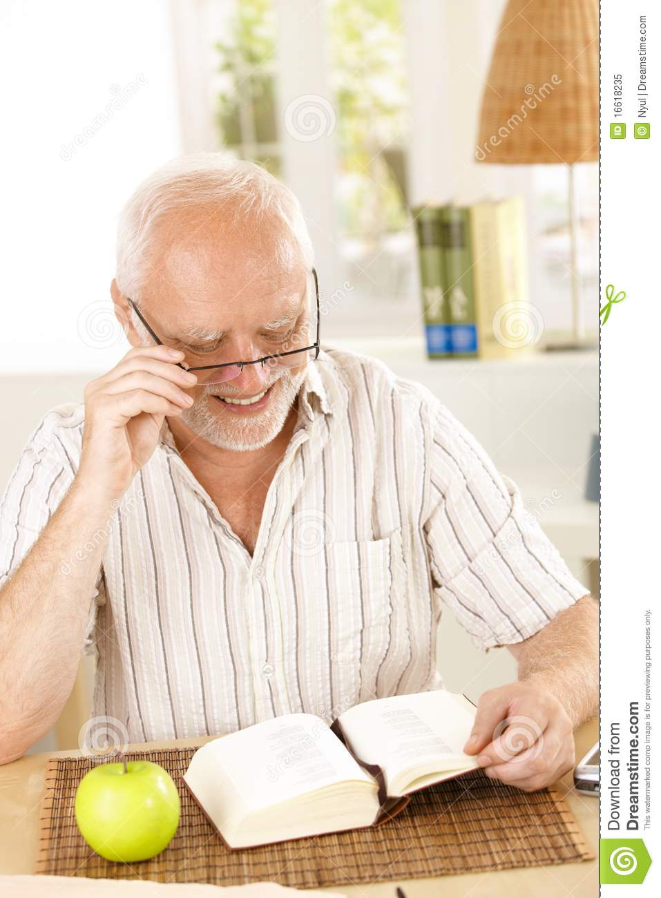 Laughing pensioner reading book