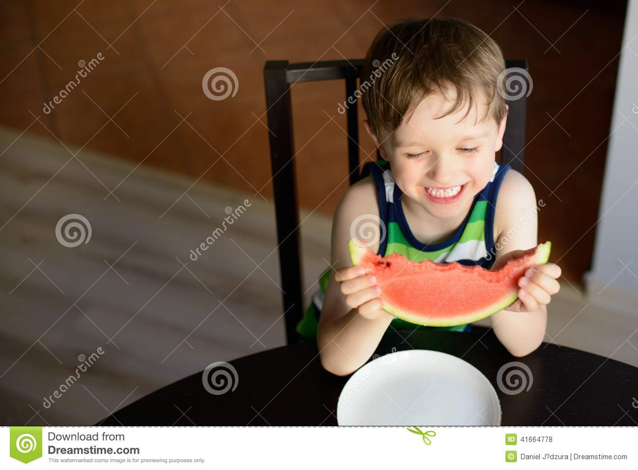 Laughing preschooler eats a watermelon at the table