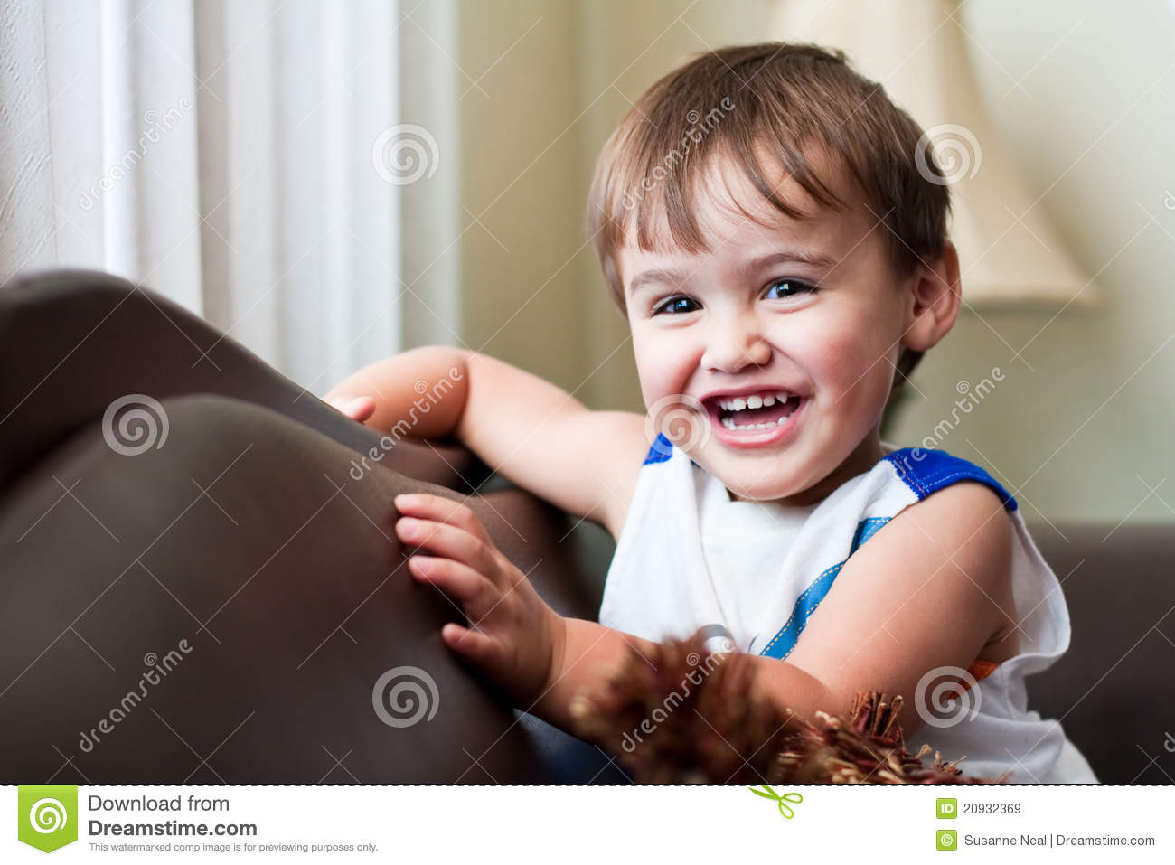 laughing toddler boy with brown hair royalty free stock