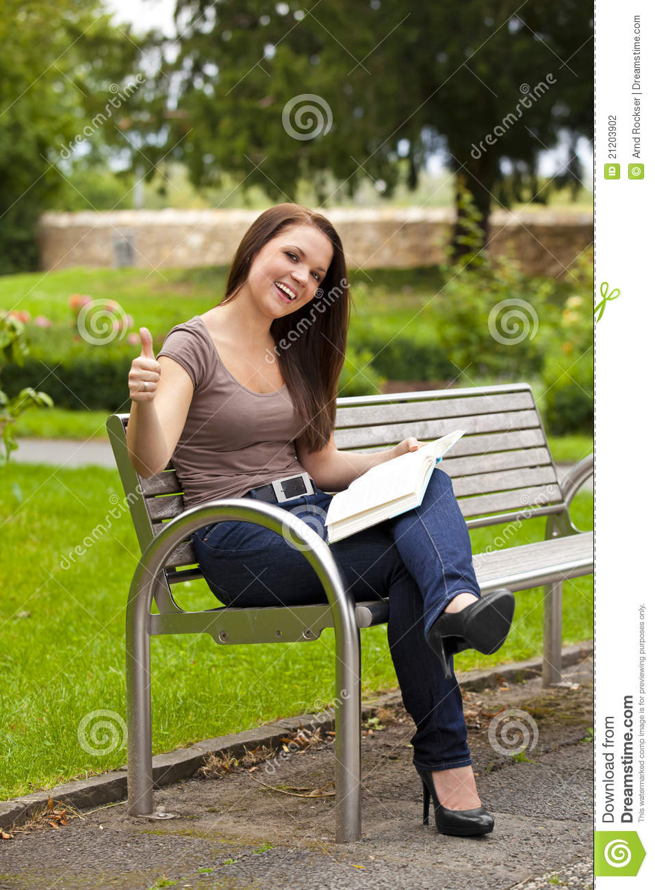 Laughing Woman With Book Posing Thumbs Up Stock Photo