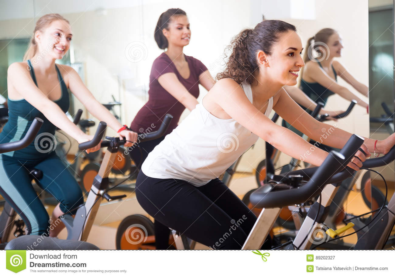 Laughing Women Of Different Age Training On Exercise Bikes Stock