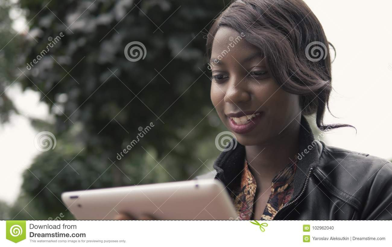 Laughing Young African American Female Holding a Touch Pad Tablet PC Outdoor, black student after university doing