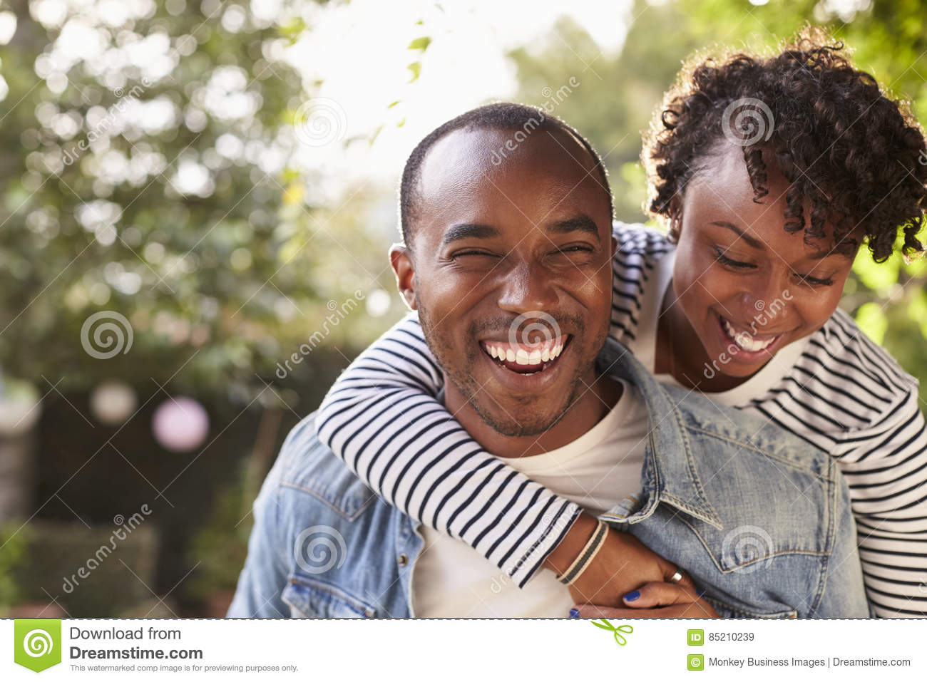 Laughing young black couple piggyback in garden, to camera