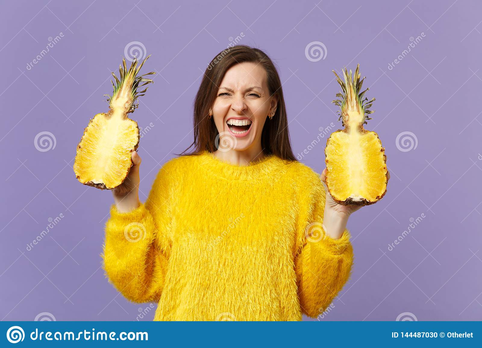 Laughing young woman in fur sweater holding in hands halfs of fresh ripe pineapple fruit isolated on violet pastel wall