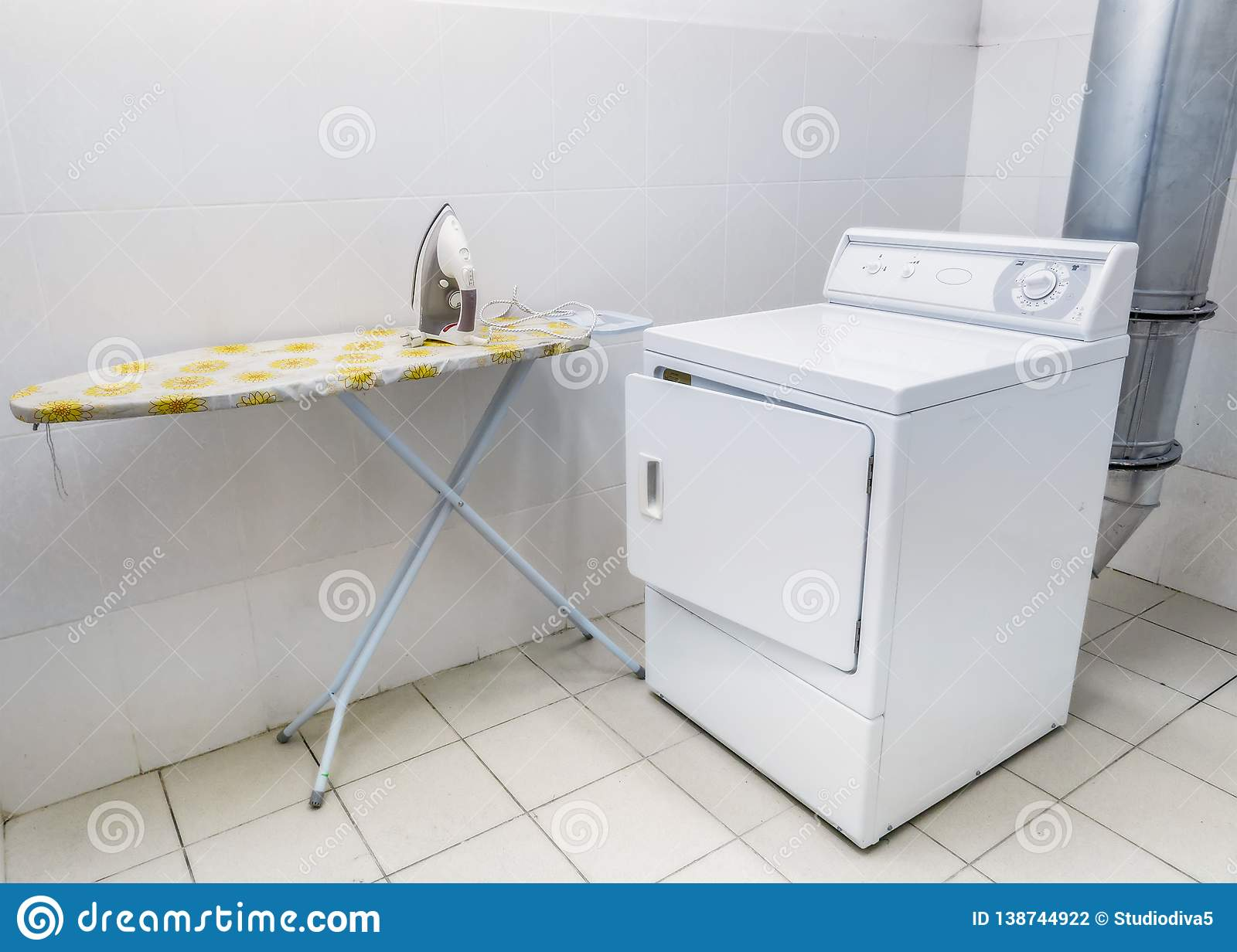 Laundromat. Laundry room for clothes. Iron and washing machine