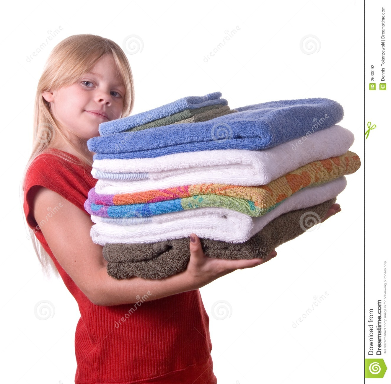 Young girl helping with laundry carrying towels.