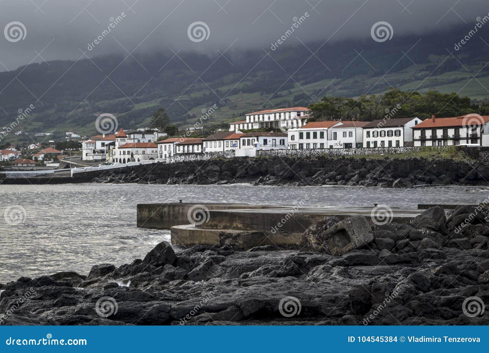 Lava rocky coastline with the original white harbor houses at sunrise on the island of Pico