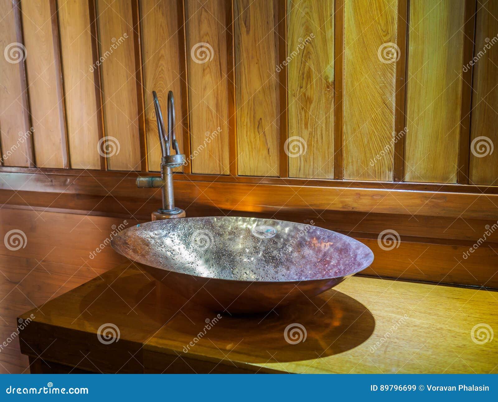 lavabo de cobre amarillo del vintage en cuarto de bao de madera foto de archivo