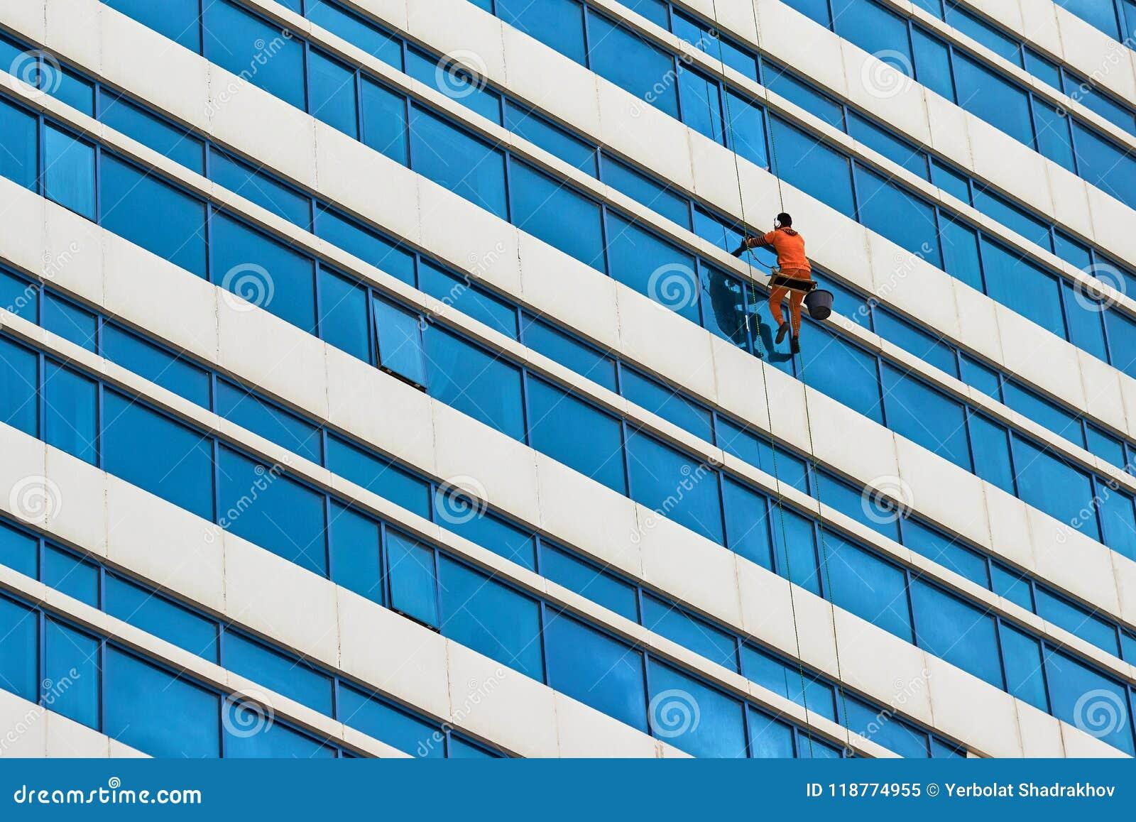 Lavado industrial del escalador las ventanas del rascacielos