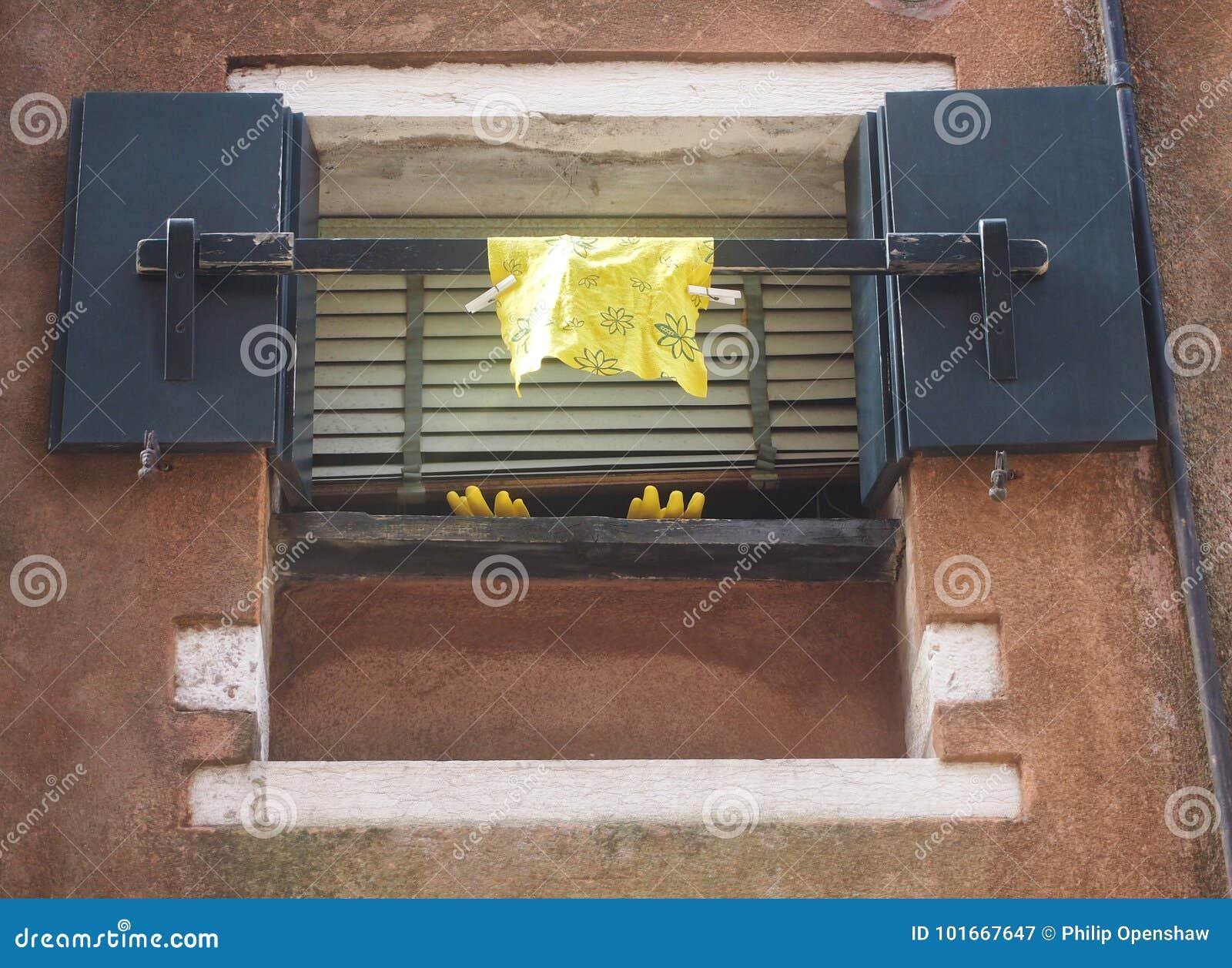 Lavage jaune vers le haut des gants et du tissu accrochant hors d une fenêtre