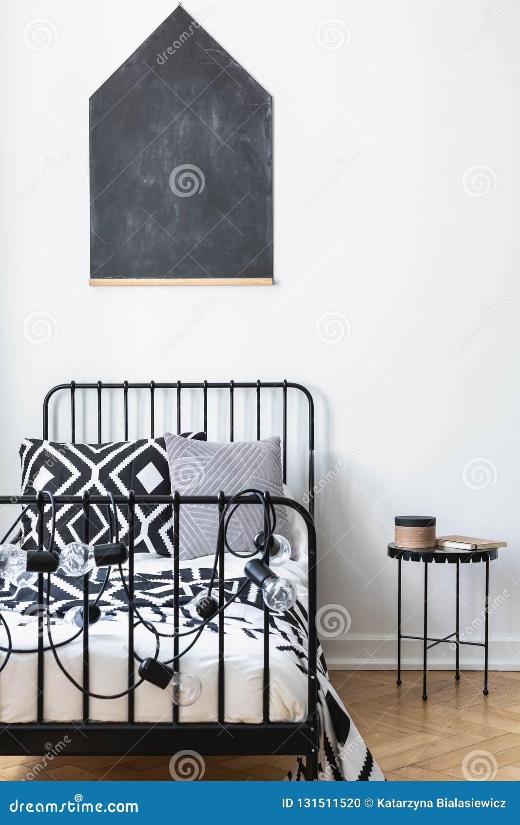 Lavagna sulla parete della camera da letto degli adolescenti con lettiera modellata in bianco e nero sul singolo letto del metall