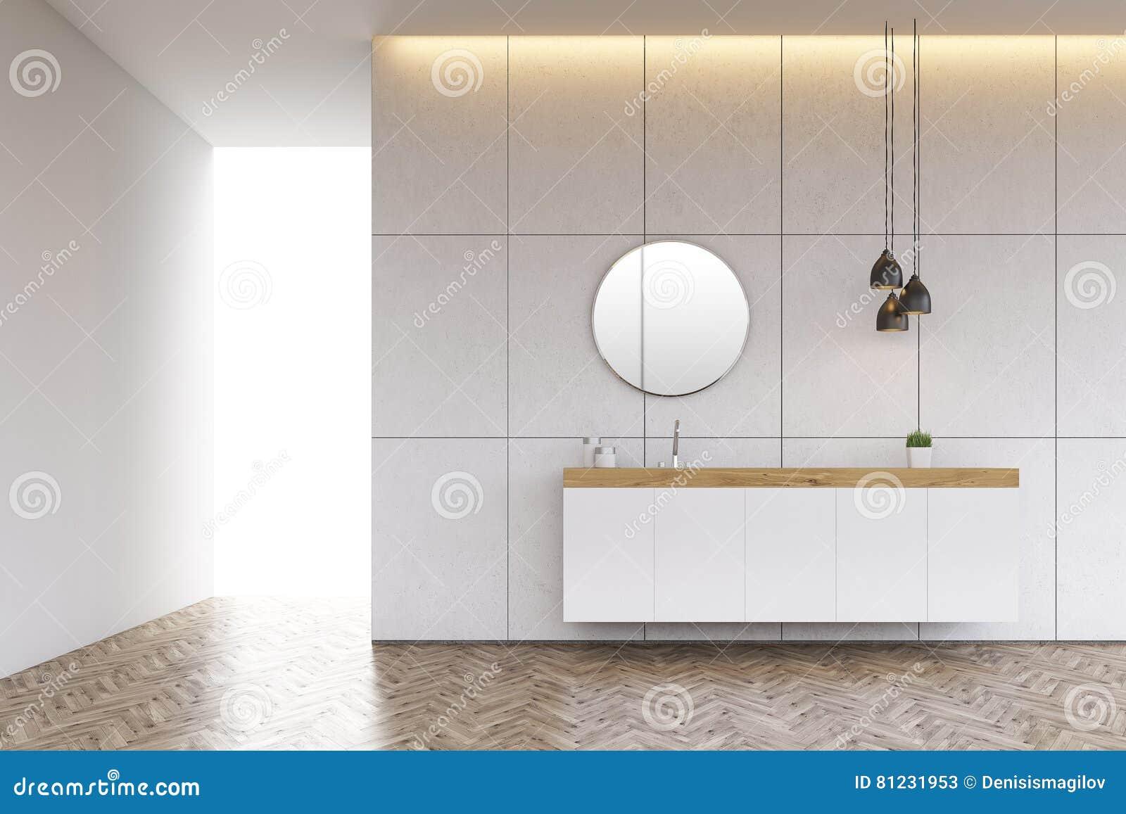 Lavandino del bagno con lo specchio rotondo sulla parete