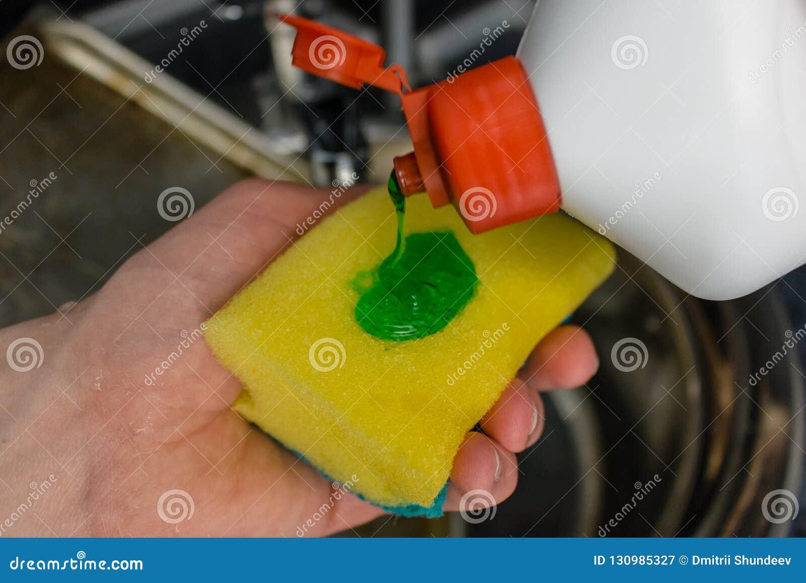 Lavatura dei piatti di versamento liquida sulla spugna