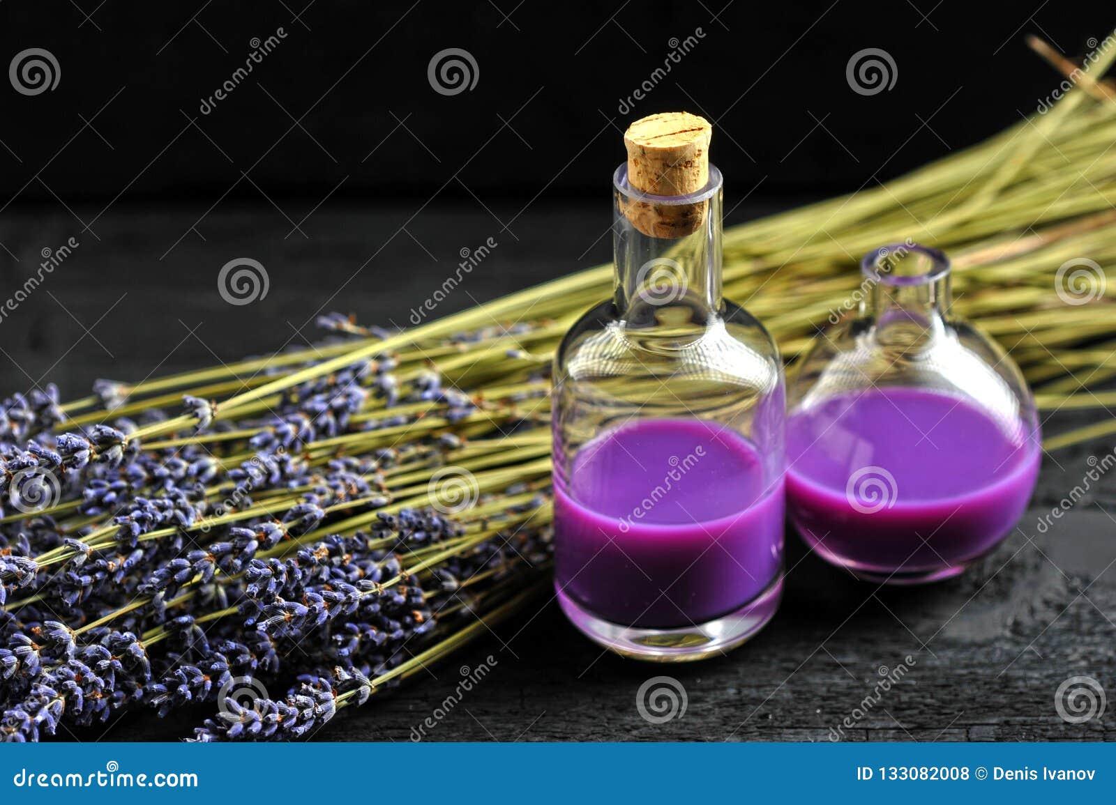 Lavendel, Lavendelöl auf dunklem hölzernem Hintergrund
