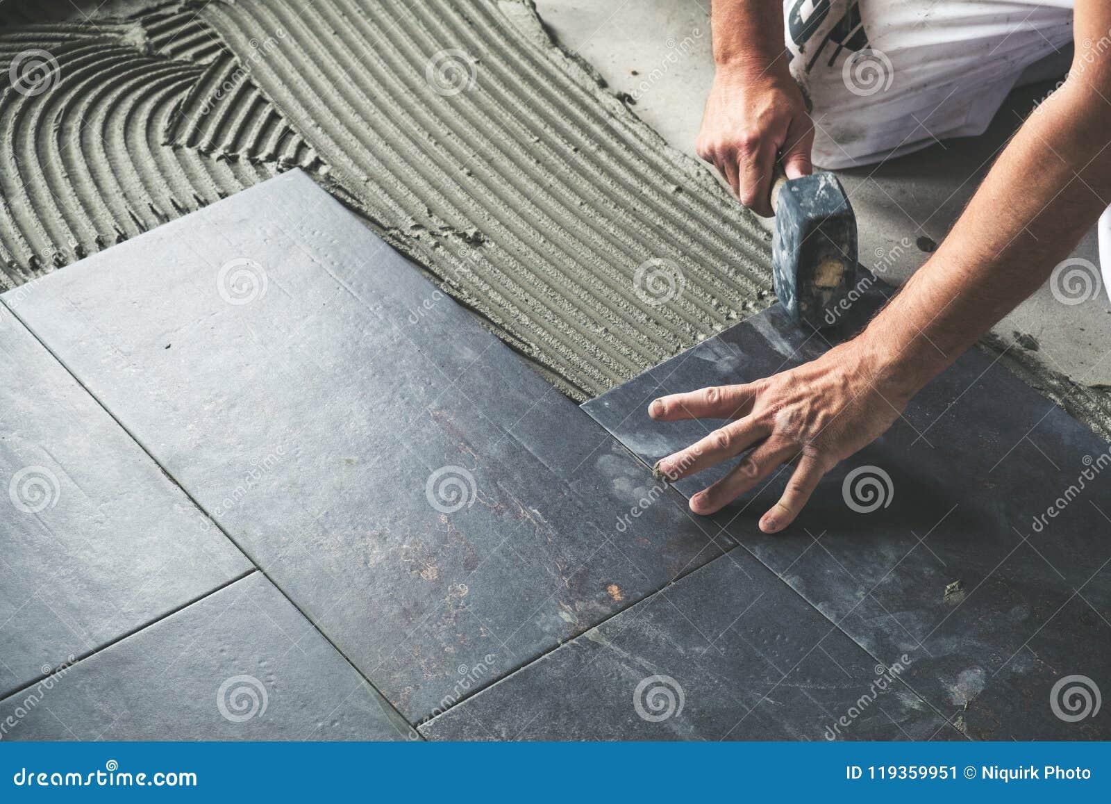 Lavoratore che dispone le piastrelle per pavimento ceramiche sulla