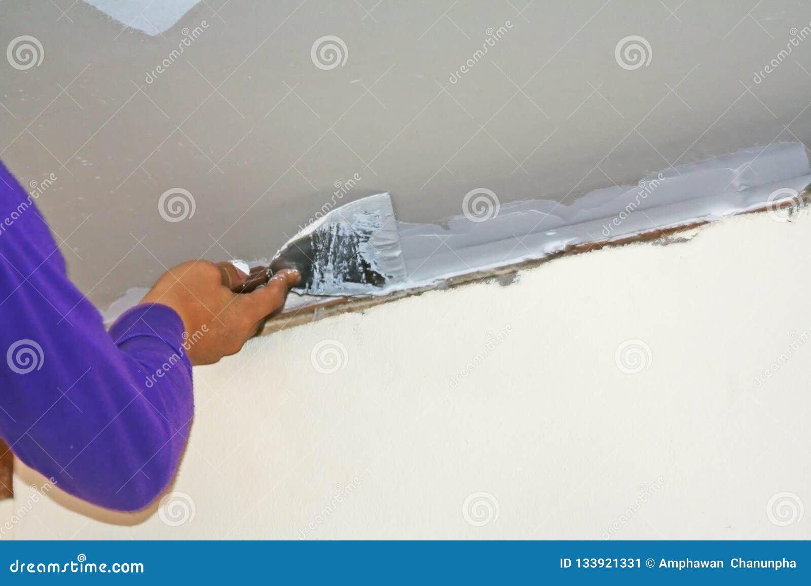 Lavoratore che usando il gesso del gesso sul coltello di mastice al soffitto