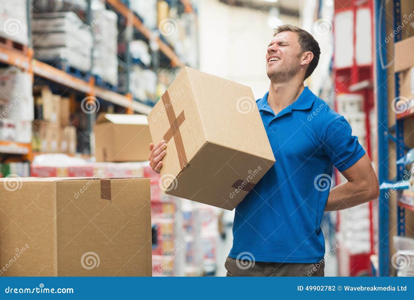 Lavoratore con il mal di schiena mentre sollevando scatola in magazzino