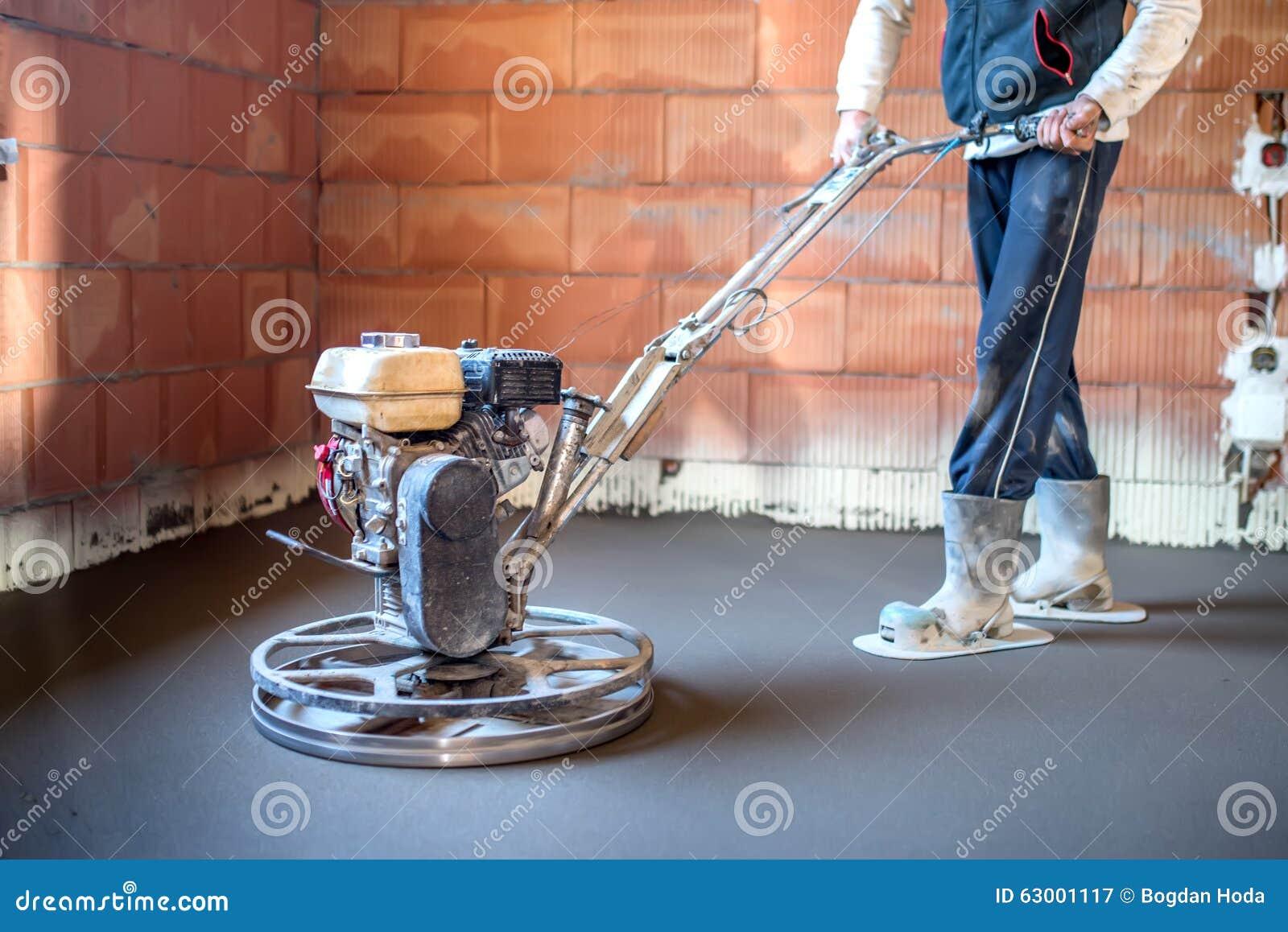 Lavoratore con lo strumento della cazzuola di potere che finisce pavimento di calcestruzzo, superficie di calcestruzzo regolare a