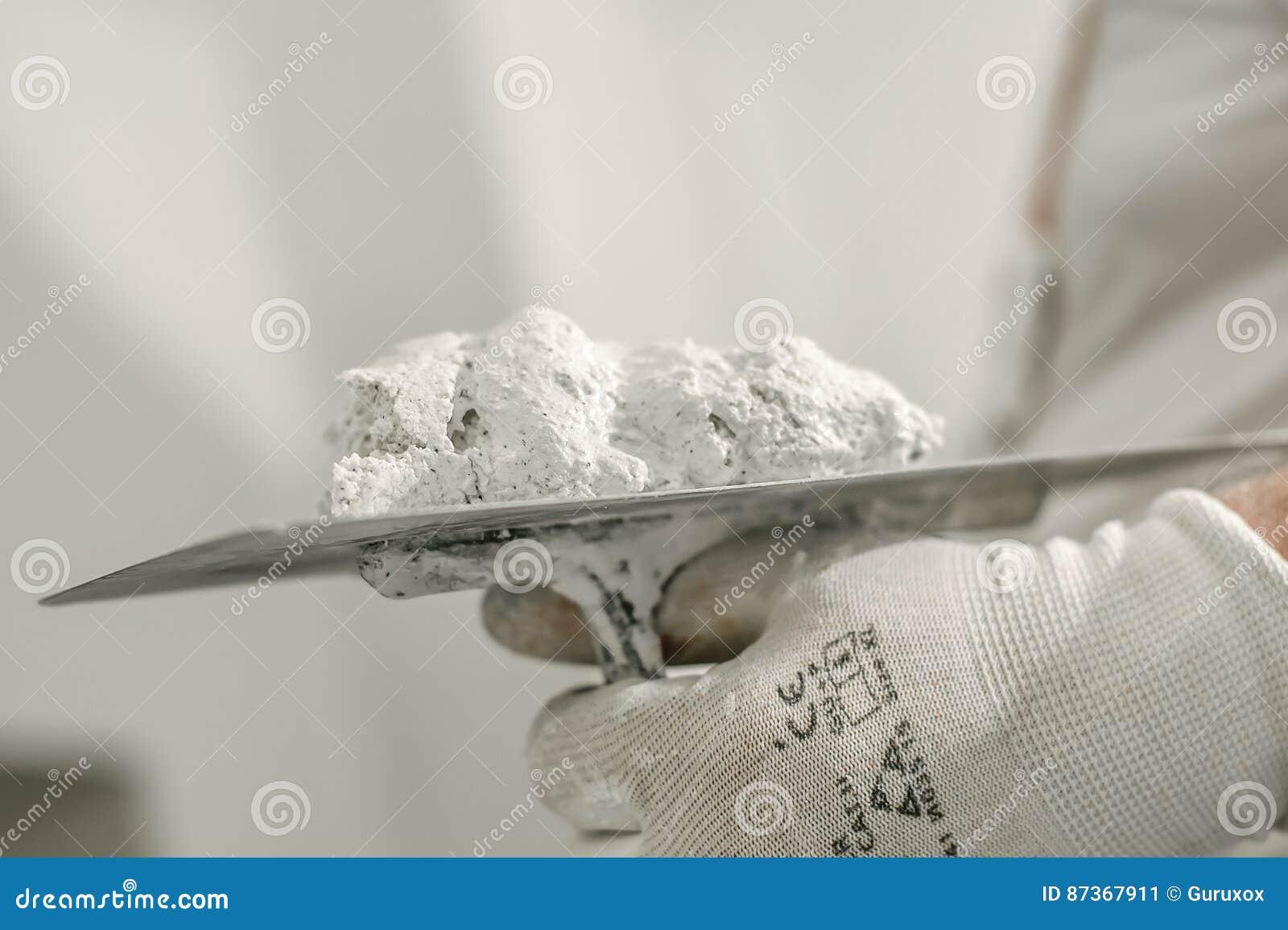 Lavoratore del muratore della costruzione con la spatola ed il mortaio