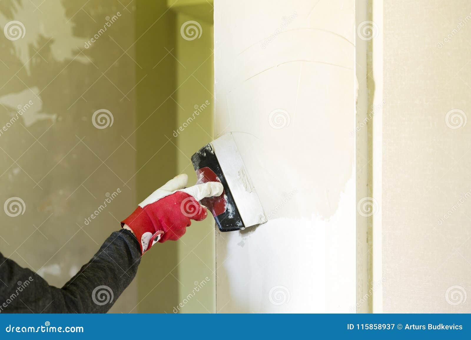 Lavoratore del tuttofare di miglioramento domestico dell intonacatore con il coltello di mastice che lavora al materiale da ottur