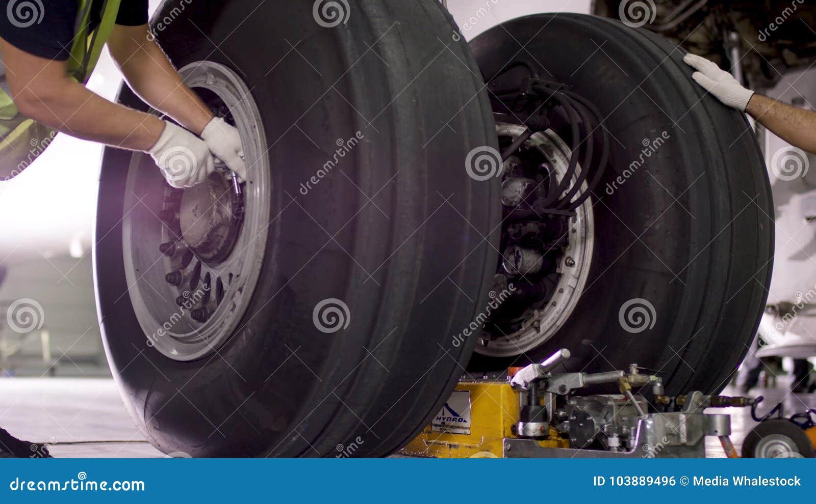 Lavoratore dell aeroporto che controlla il telaio Motore e telaio dell aeroplano del passeggero nell ambito di manutenzione pesan