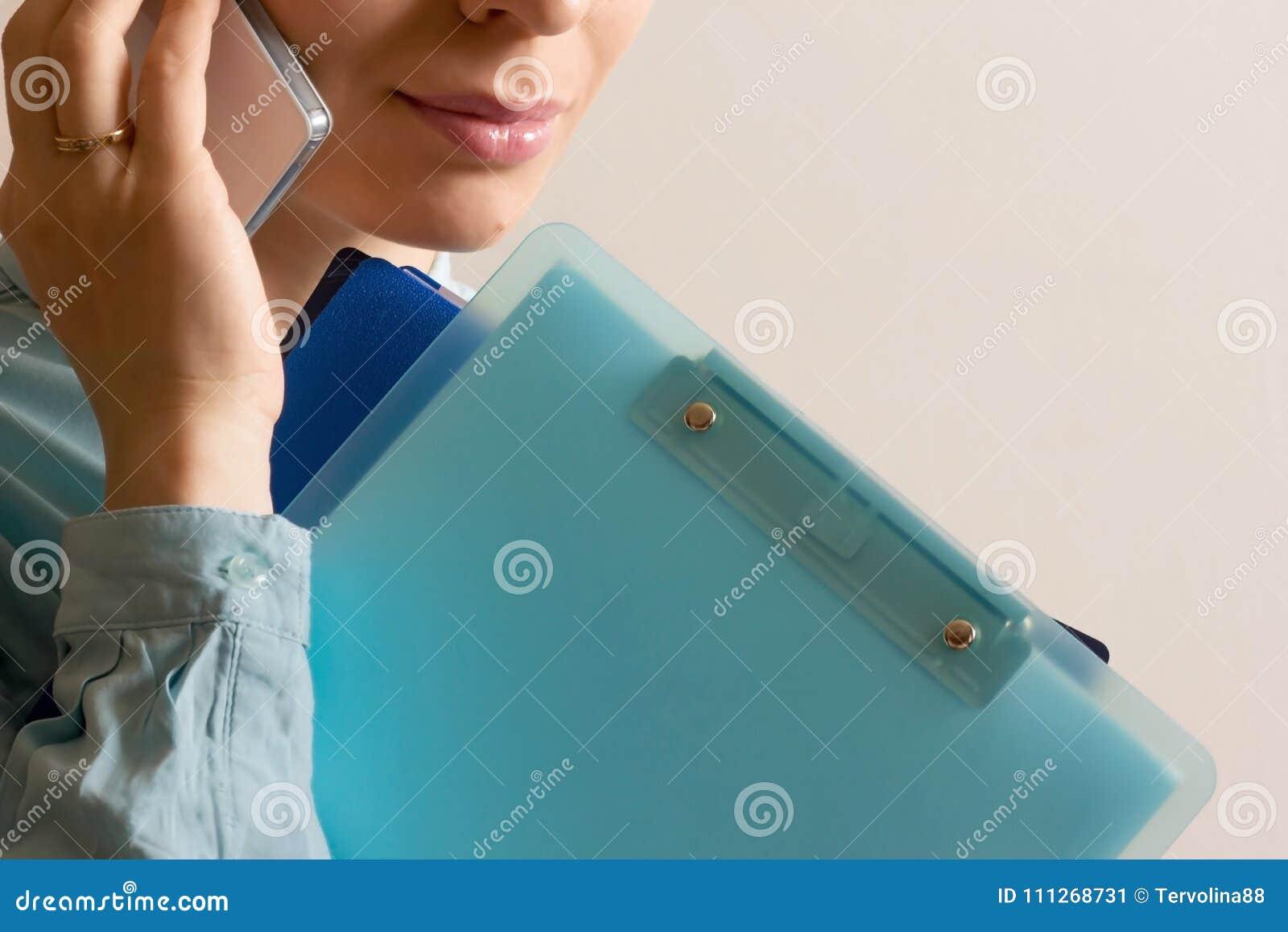 Lavoratore dell donna-ufficio che parla sul telefono con i lotti delle cartelle a disposizione