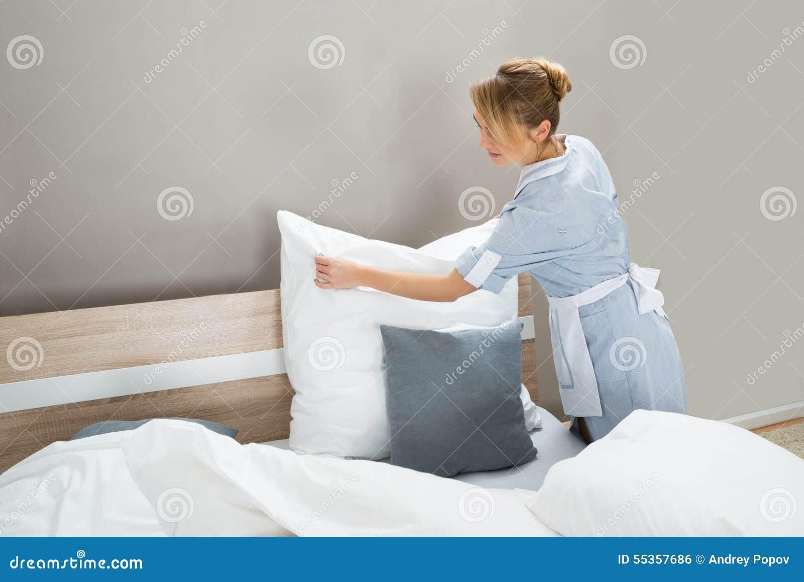 Lavoratore di governo della casa che mette i cuscini bianchi