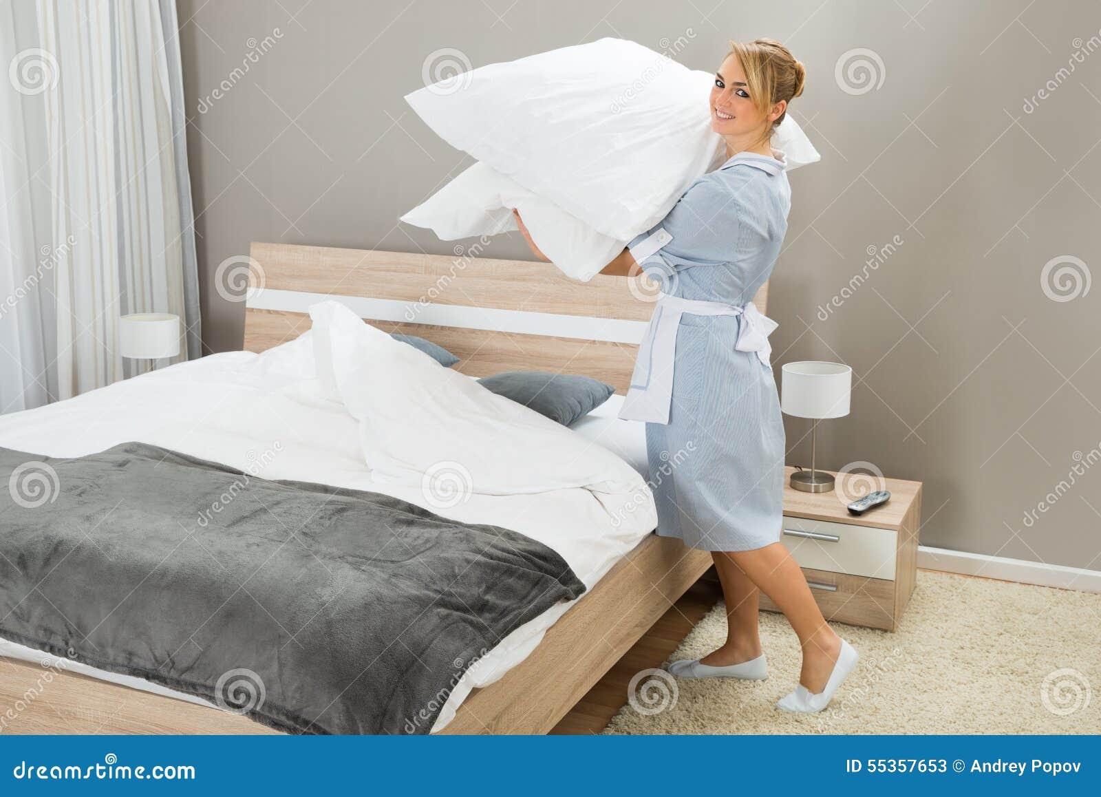 Lavoratore di governo della casa con i cuscini