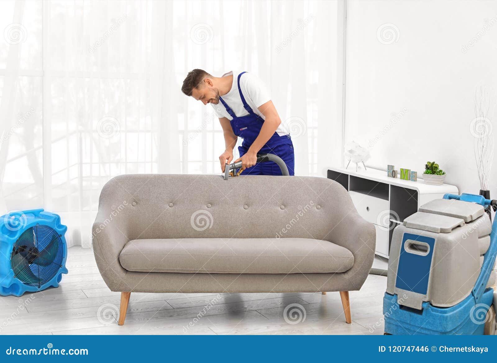 Lavoratore di lavaggio a secco che rimuove sporcizia dal sofà
