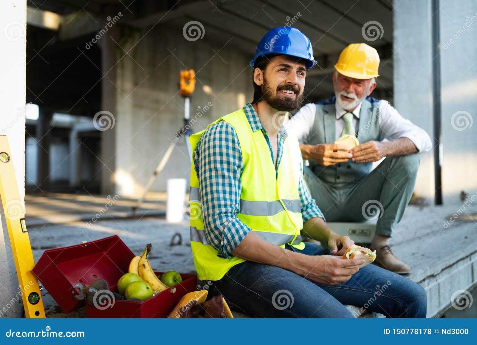 Lavoratore felice del giovane ed ingegnere senior che si siede al cantiere sulla rottura
