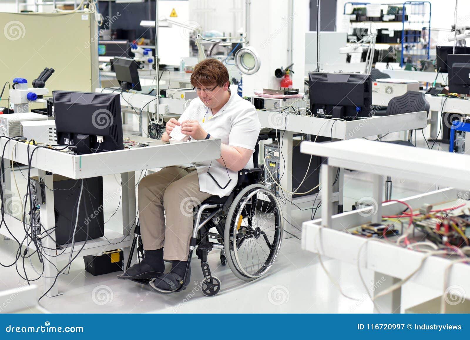 Lavoratore handicappato in una sedia a rotelle che monta compone elettronico