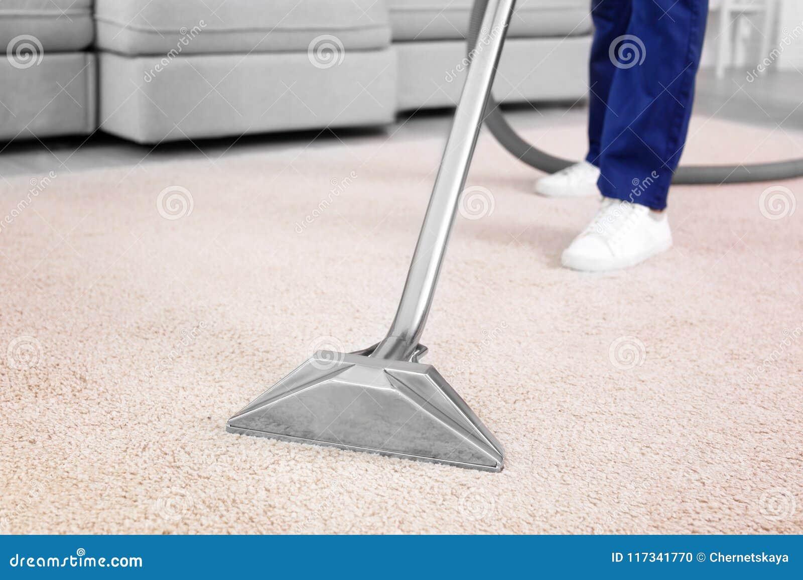 Lavoratore maschio che rimuove sporcizia dal tappeto