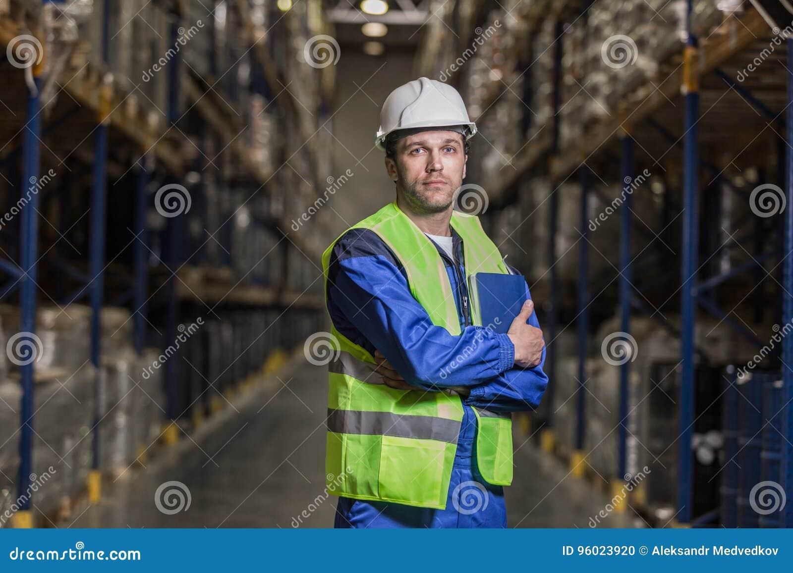 Lavoratore maschio che sta fra gli auto con il taccuino