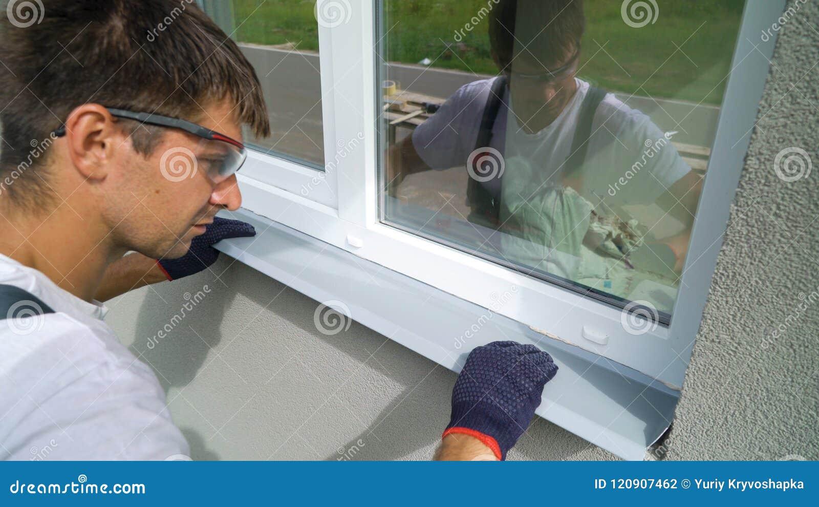 Lavoratore negli occhiali di protezione ed in guanti protettivi che installano il davanzale del metallo sulla struttura della fin