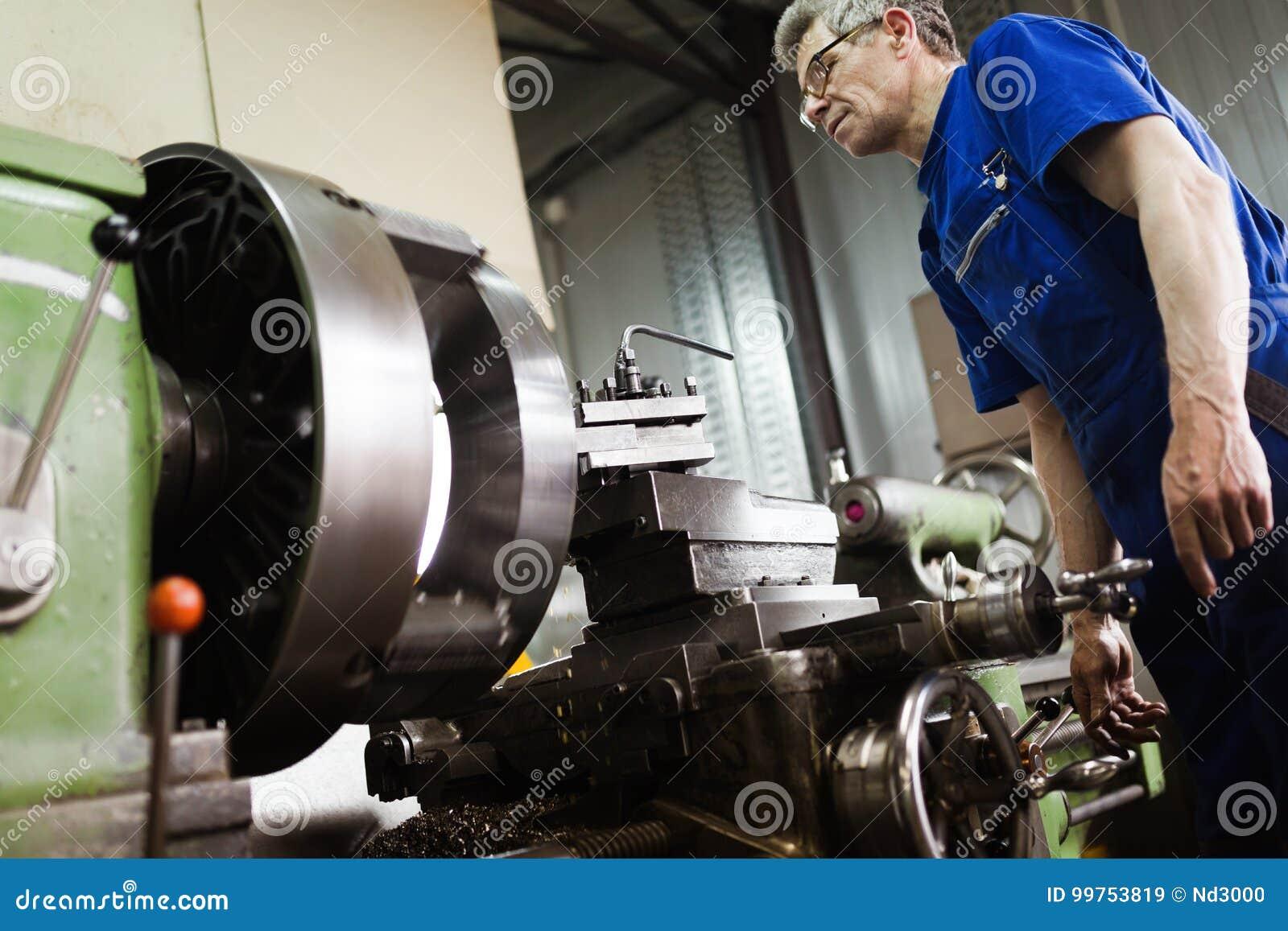 Lavoratore in uniforme che funziona in tornio manuale nella fabbrica dell industria metalmeccanica