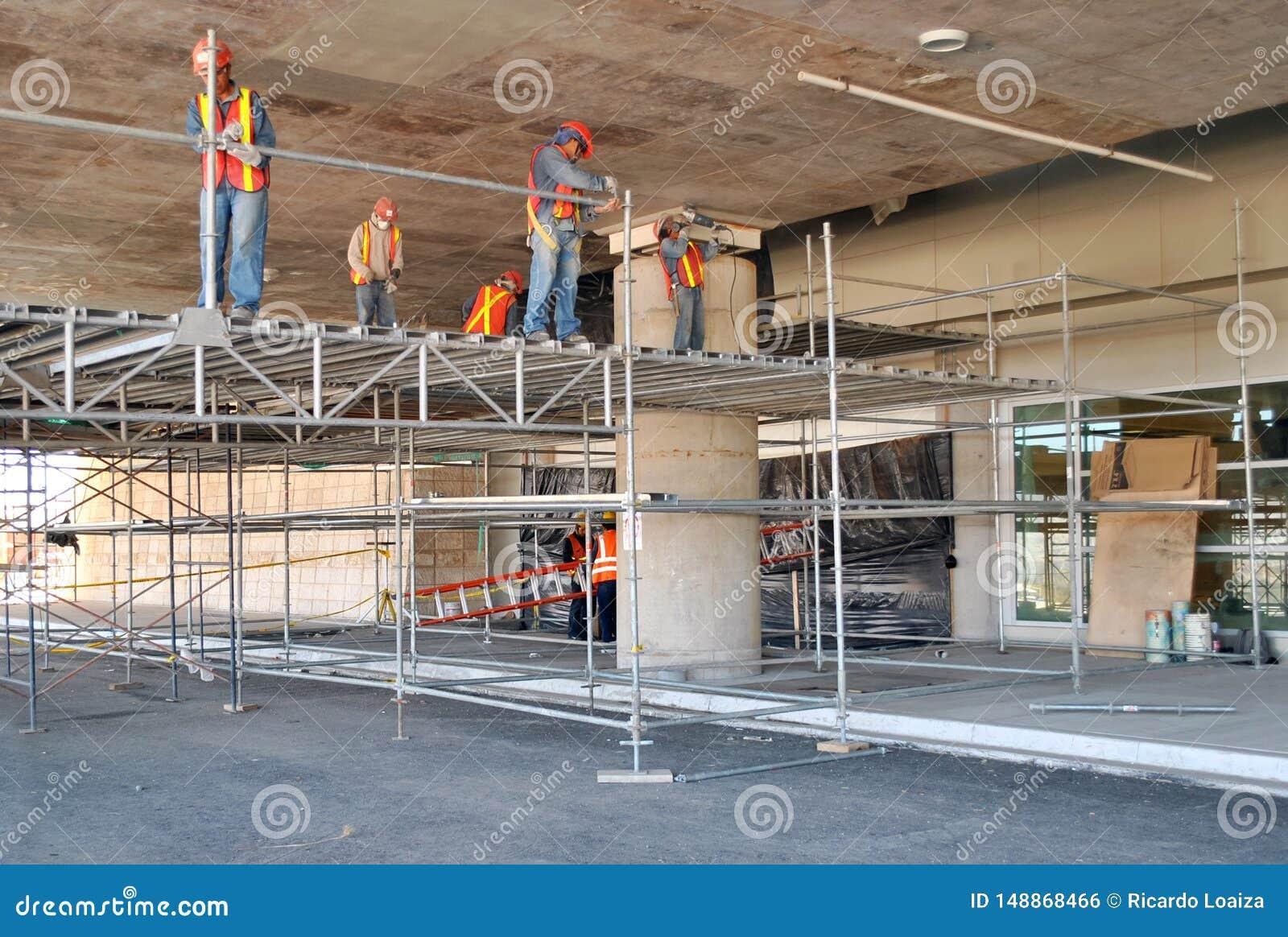 Lavoratori che montano armatura e che lavorano al tetto di un parcheggio in costruzione