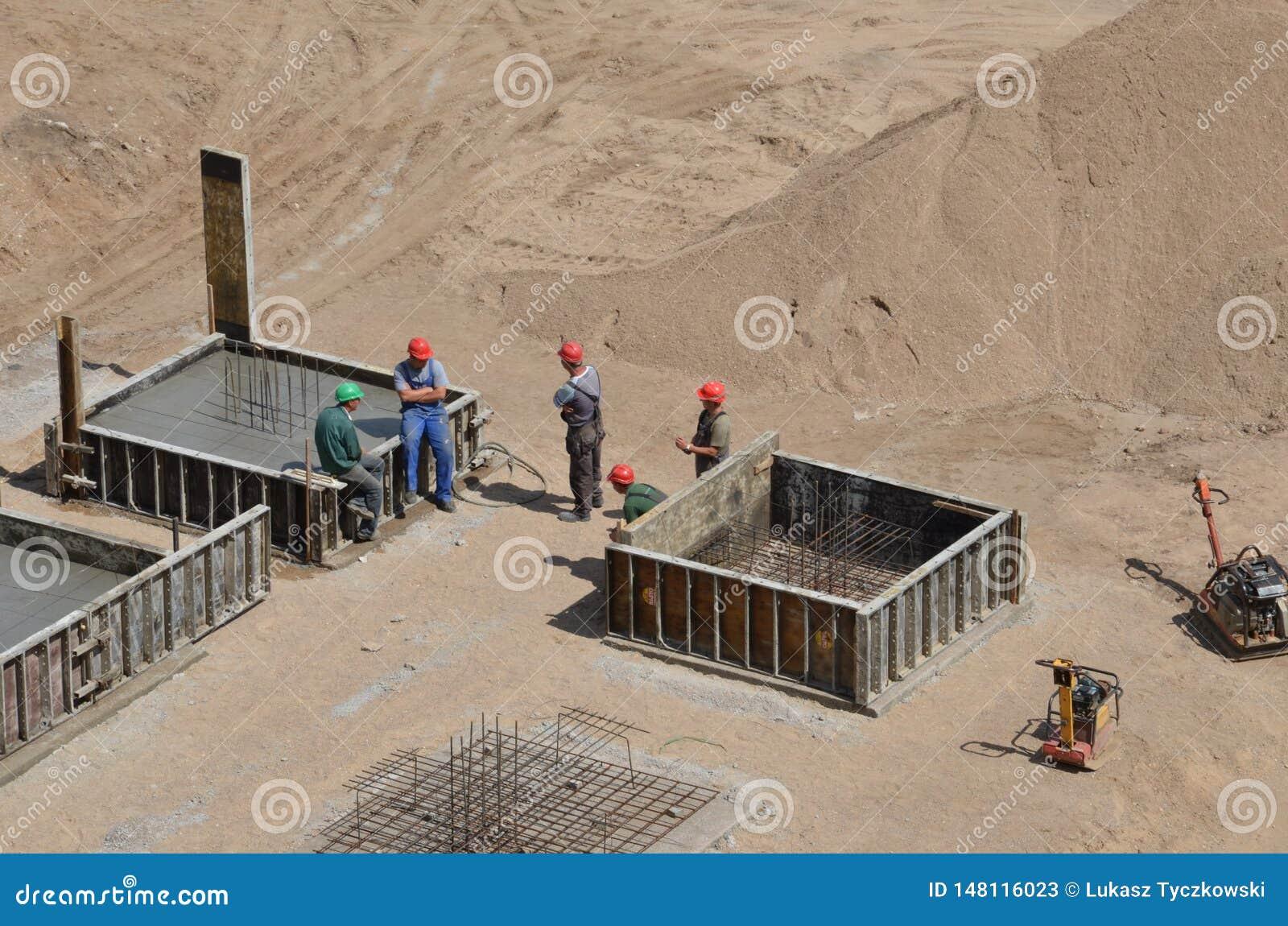 Lavoratori che stanno al cantiere che ha una conversazione durante la pausa